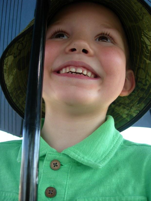 Connor smiling up at umbrella