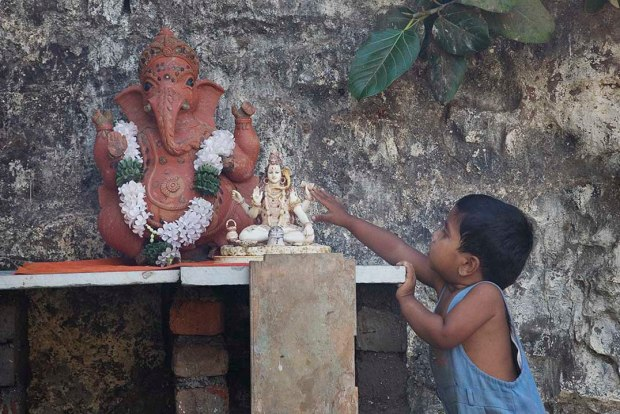 Hindu boy reaching for Ganesh in Mumbai, India by Steve Evans